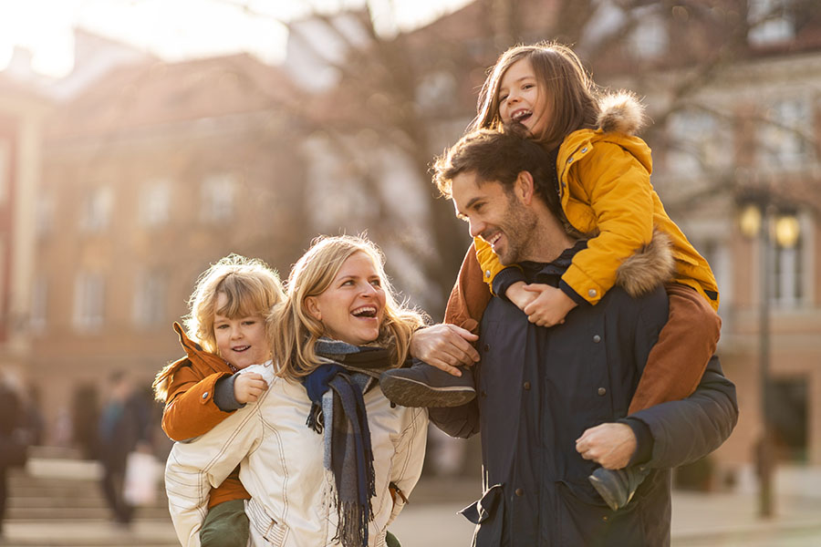 Personal Insurance - Smiling Family Having Fun Taking A Walk Outside In The City